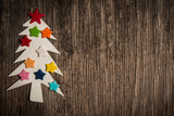Christmas tree made of paper and hearts on wooden background