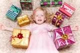 Девочка лежит на полу, окружённая коробками с рождественскими подарками