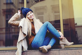 Fototapety Outdoor full body portrait of young beautiful happy smiling girl posing on street. Model looking at camera. Lady wearing stylish winter clothes. Female fashion. Toned