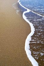 Vague douce de l'océan bleu sur la plage de sable fin. Contexte.