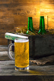 mug of beer with the old box of beer and bottles on wooden background