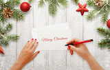 Woman write Christmas greeting card. Christmas tree with decorations beside. White wooden surface in background.