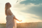 a new day begins with the sunrise protected in the hands of a woman - 128144628