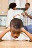 Sad boy against parents arguing