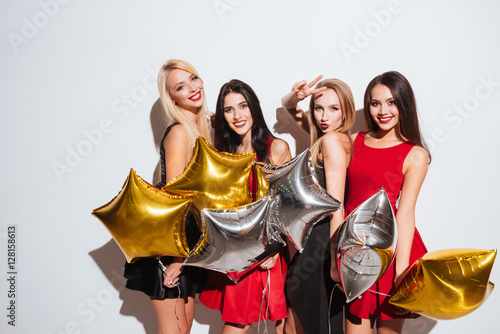 Plakát, Obraz Four smiling attractive girls standing and holding star shaped balloons
