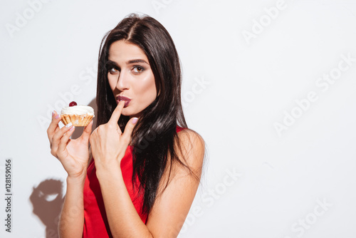 Poster Cute attractive young woman standing and holding cupcake