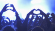 Hands of concert crowd forming heart at live music concert, festival