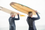 Senior couple in wetsuit carrying surfboard over head