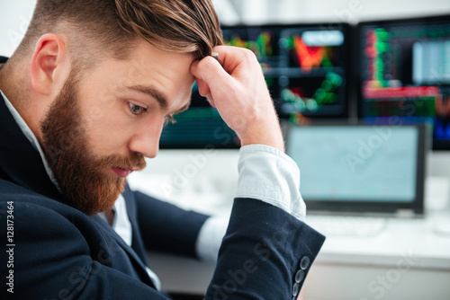 Poster Pensive bearded young businessman sitting and thinking in office