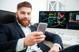 Happy bearded young businessman sitting and using mobile phone