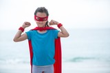 Girl wearing superhero costume flexing muscles at beach