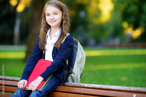 Fotografiet Adorable little schoolgirl in a city park