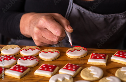 Poster woman decorating gingerbread christmas cookies