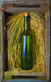 green bottle of wine in an old box with straw