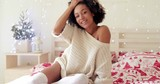 Cute young woman with a sweet smile relaxing on her bed in a festive Christmas bedroom grinning at the camera in a stylish knitted winter top.