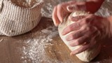 Making bread - woman hands kneading the dough, closeup