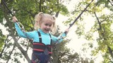 Little girl bouncing up and down on a bungee trampoline. Slow Motion.