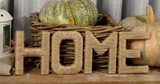 Letters drawn up in the form of the word HOME with pumpkins, pine cones and lanterns. 4K