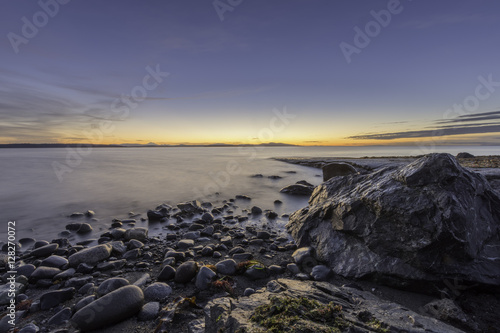 Valokuva First light at the shoreline with rocks sand blue sky and smooth water