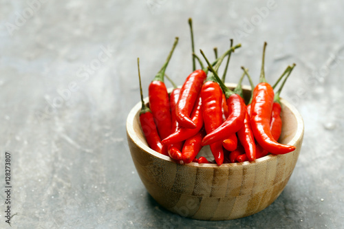 Poster fresh red chili peppers in a wooden bowl