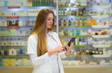 Happy young woman pharmacist over drugstore background, holding digital tablet