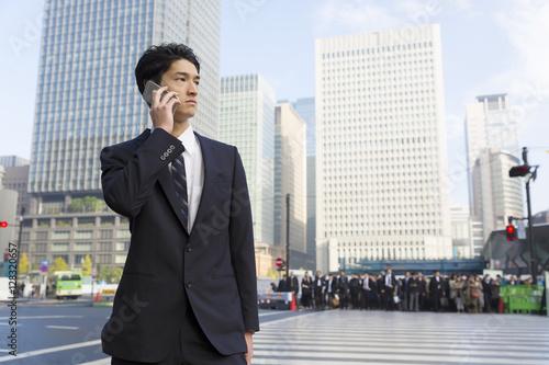 Poster 男性 ビジネスマン スマホ 話す 外 東京駅前 朝 大勢の通勤客背景