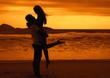 Liebespaar umarmt sich bei Sonnenuntergang