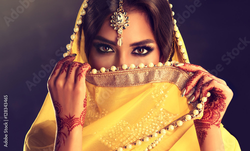 Foto Murales Beautiful indian girl . Young hindu woman model  with tatoo mehndi  and kundan jewelry . Traditional Indian costume yellow saree . Indian or Muslim woman covers her face.