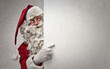 Santa Claus indicating a white cardboard