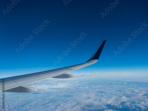 Wing of an airplane flying above the clouds on a clear sunny day - 128364211