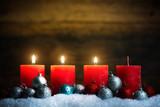 Weihnachtsschmuck und 4 Kerzen von denen drei symbolisch für den 3. Advent leuchten