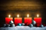 Weihnachtsschmuck und 4 Kerzen die symbolisch für den 4. Advent leuchten