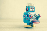 Old robot toy on wood table, vintage color style, vintage tone background.