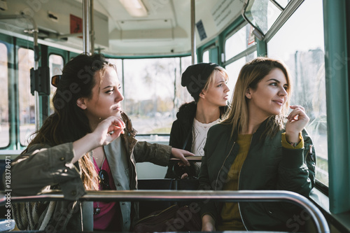 Three beautiful young women sitting in tram and looking through window