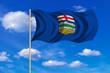 Flag of Alberta waving on blue sky background
