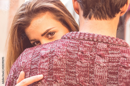 Foto Murales Attractive girl hugging her boyfriend and looking at the camera
