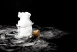 White smoke inside glass bottle at black background, Mistery hal