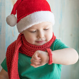 Adorable boy in Santa hat looking time