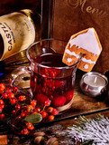 Mulled wine of warming white wine with wine bottle. Label on bottle of wine. Bottle lying on wooden table. Ginger snap in form of house decorated cider. Menu card background.