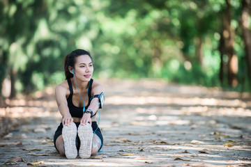 Young fitness woman stretching legs before run.