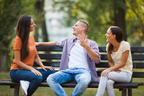 Three friends are sitting on bench in park and talking.