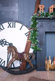Wooden horse and clock with Christmas decoration on wooden background in vintage style,