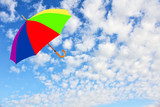 Multicolored umbrella flies in sky against of pure white clouds.Wind of change concept.