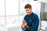 Young man using a smartphone and smiling indoors - 128467472