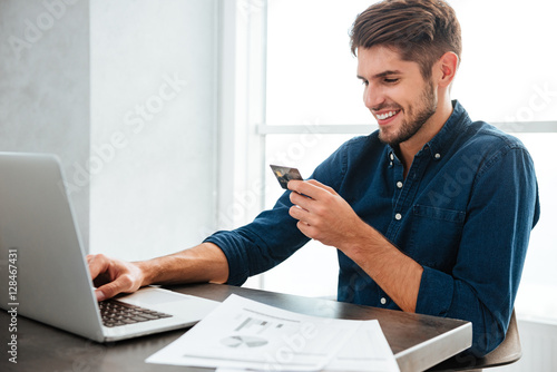 Young man holding a credit card and typing