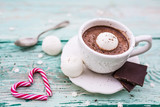 Delicious hot chocolate with marshmallows in a cup on a wooden table.