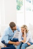 Man comforting her woman in living room