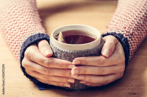 Hot mug of tea warming woman's hands in retro jumper.