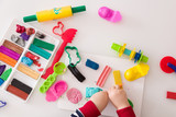 Child's hands with colorful clay. Toddler playing and creating toys from play dough. Boy molding modeling clay. - 128482441