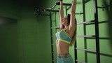 Strong woman make exercise for abdominal muscles on horizontal bar